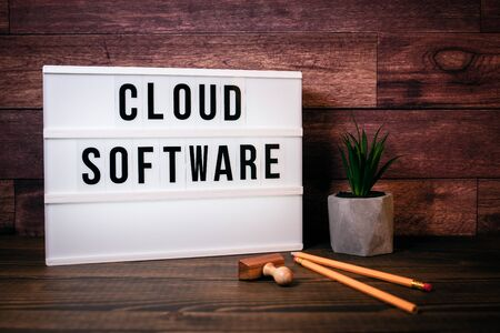 Cloud software. Text in lightbox. Wooden office table