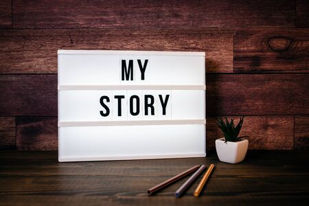My Story. Text in lightbox. Wooden office table Stock Photo - 125886839