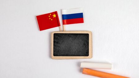 Russian and Chinese flags. Small whiteboard with chalk. Top view on a white background. Mockup, copy space