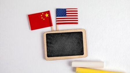 United States of America and Chinese flags. Small whiteboard with chalk. Top view on a white background. Mockup, copy space Stock Photo - 125886802