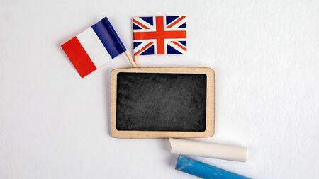 British and French flags. Small whiteboard with chalk. Top view on a white background. Mockup, copy space Stock Photo
