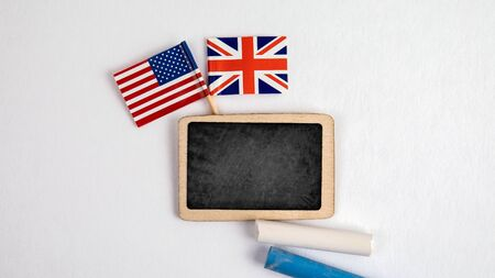 British and United States Of America flags. Small whiteboard with chalk. Top view on a white background. Mockup, copy space Stock Photo - 125886806