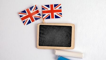 British flags. Small whiteboard with chalk. Top view on a white background. Mockup, copy space Stock Photo - 125886808