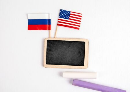United States and Russia flags. Small whiteboard with chalk. Top view on a white background. Mockup, copy space Stock Photo