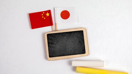 Japan and Chinese flags. Small whiteboard with chalk. Top view on a white background. Mockup, copy space