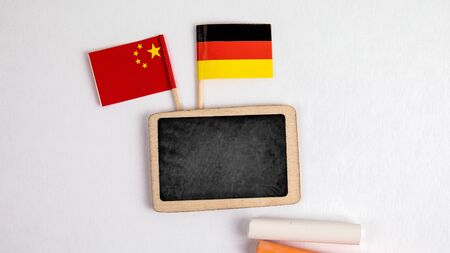 Germany and Chinese flags. Small whiteboard with chalk. Top view on a white background. Mockup, copy space Stock Photo - 125886812