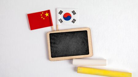 Republic of Korea and Chinese flags. Small whiteboard with chalk. Top view on a white background. Mockup, copy space Stock Photo - 125886813
