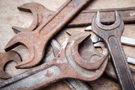 Wrench, different sizes, old and rusty. Construction and hand tools on wooden board, maintenance and reparing concept
