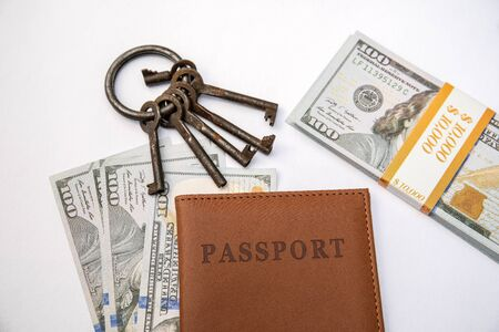 Bunch of different keys, passport and money on a white background. New housing, property and mortgage loan concept. Copy space Stock Photo - 125886791