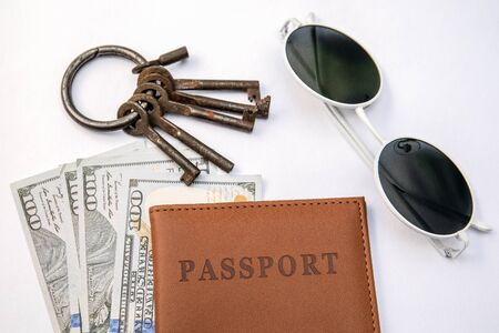 Bunch of different keys, passport and money on a white background. New housing, property and mortgage loan concept Stock Photo - 125886797