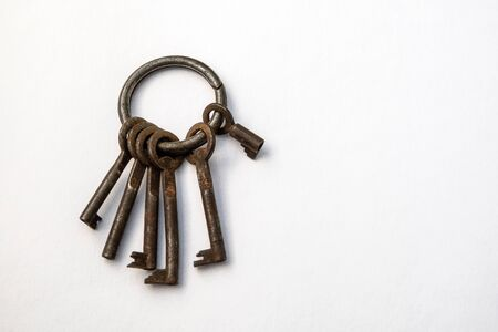 Bunch of different keys on a white background. New housing, property and mortgage loan concept. Copy space