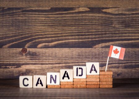 Canada. Politics, economic and immigration concept. Wooden letters and flag on the office desk