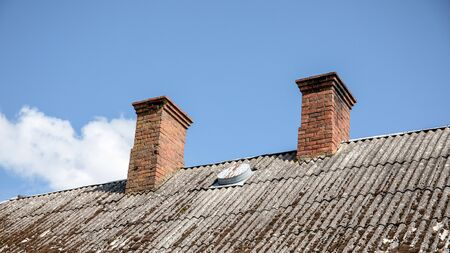 Chimney on a roof of an old residential house. Blue sky and white cloud