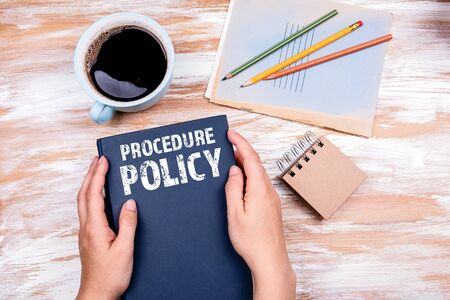 Procedure and Policy concept. Hands holding book on office table