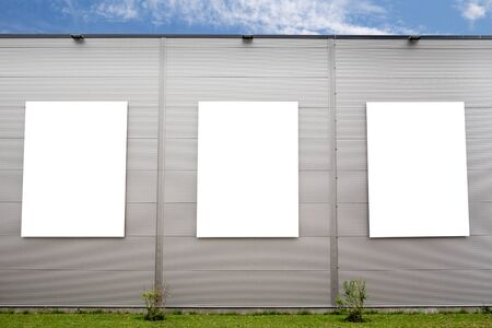Three big vertical poster on the grey building. Empty advertising frame, mockup