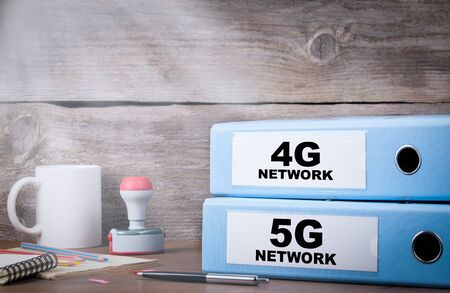 5G and 4G network. Two binders on desk in the office. Business background