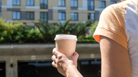 Woman Holding takeaway coffee cup, apartment and office building in the background.