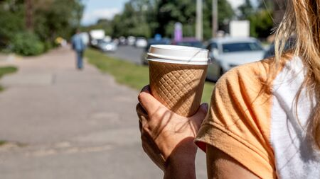 Woman Holding takeaway coffee cup on the street.