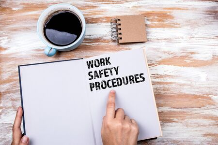 Work Safety and Safety Procedures concept. Hands holding book on office table