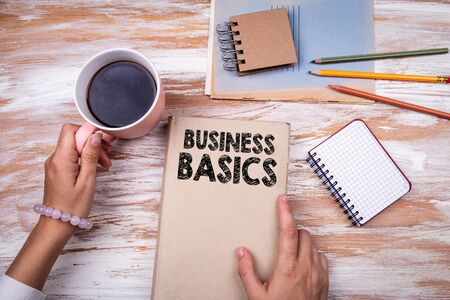 Business Basics. Hands holding book on office table