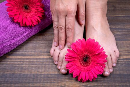 Pedicure. Womens legs and hands on the background of towel and flowers