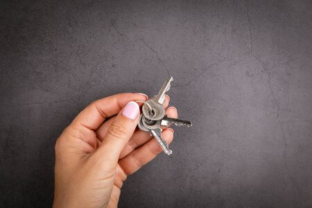Closeup of hand holding a key. New house or apartment, a mortgage loan and moving concept