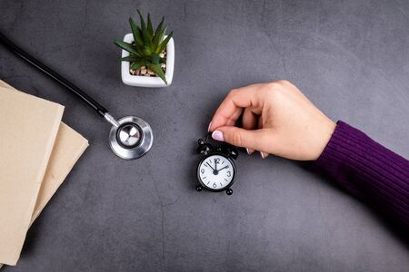 hand of woman holds alarm clock. Books and stethoscope on concrete table. Medicine, health care and insurance concept Banco de Imagens
