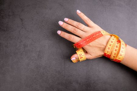 Woman's hand with measuring tape. Weight watching, healthy lifestyle and fitness concept