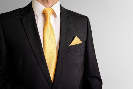Hombre de negocios con traje con corbata amarilla y pañuelo de bolsillo.
