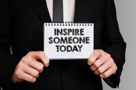 Inspire Someone Today. Positive and motivating concept. Business man with a notepad Banco de Imagens