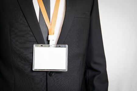 Businessman showing a white empty staff identity mockup with orange lanyard