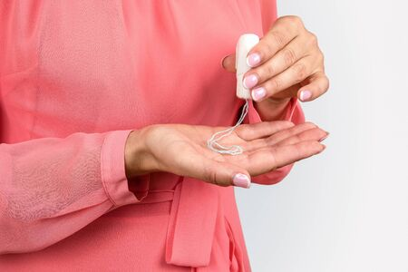 Female hygiene, secretions and menstruation protection. Woman holds sanitary tampon Banco de Imagens