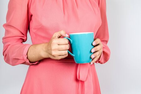 Close-up of a womans hand holding a cup of hot coffee. Pink nails and dress Banco de Imagens