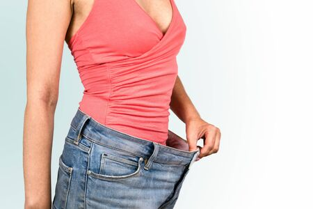 Women shows her weight loss. Too Big blue jeans