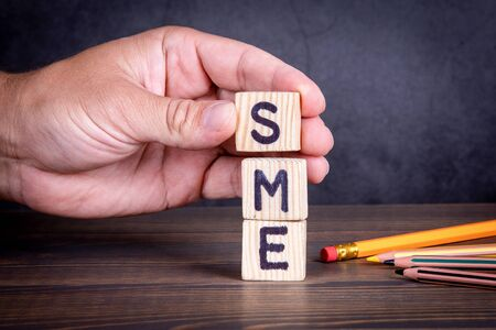 SME. Small and medium-sized enterprises concept. Wooden letters on the office desk