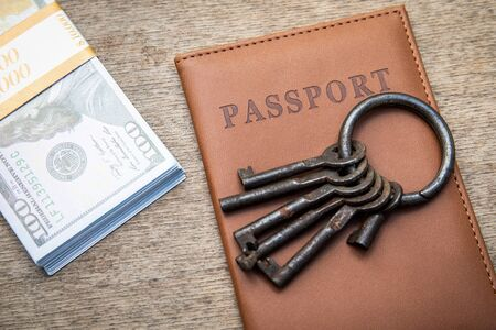 Bunch of different keys, passport and money on a wooden background. New housing, property and mortgage loan concept