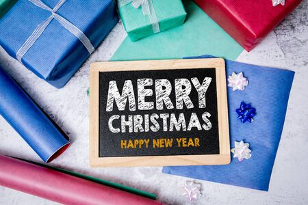 Merry Christmas and Happy New Year greetings. Chalkboard, gifts and decorations.