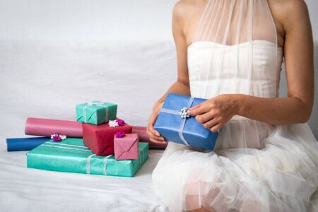 Women in ball dress preparing gifts for celebration. Gift boxes in colorful wrapping paper for Christmas, New Year or birthday party