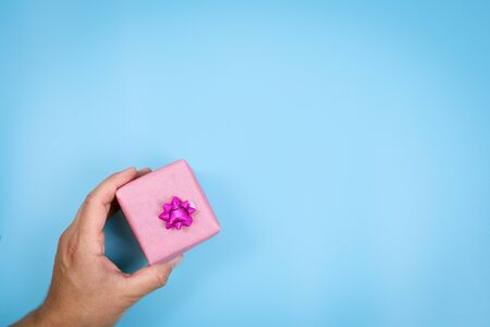 Person showing gift box. Empty blue background