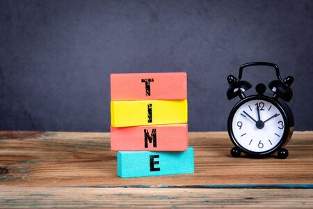 Time concept. Office table and colorful wooden blocks with text