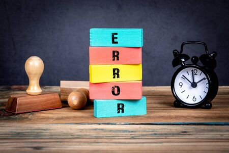 Error concept. Stamps and clock on the office table and colorful wooden blocks with text