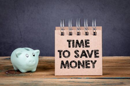 Time to save money. Piggy bank and notebook on a wooden table