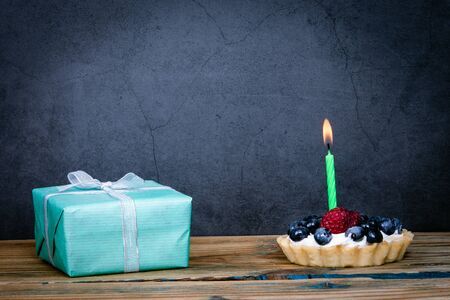 Birthday cake with berries and one lighted candle, gift box 스톡 콘텐츠
