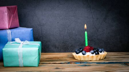 Birthday cake with berries and one lighted candle, stack of gift boxes