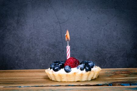 Birthday cake with berries and one burning candle.