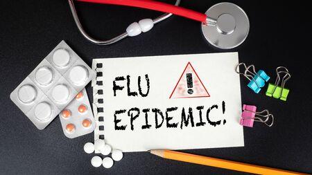 Flu Epidemic. Medicines, red stethoscope and stationery on a black table Reklamní fotografie