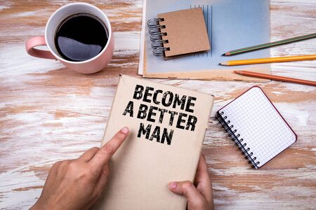 Become a Better Man. Hands holding book on office table Banco de Imagens