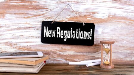 New Regulations. Mobile phone, books and hourglass.