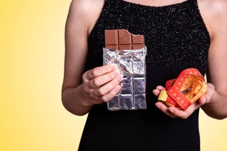 Close-up Of Hands Holding Chocolate and measure tape. Diet, health and sweets concept