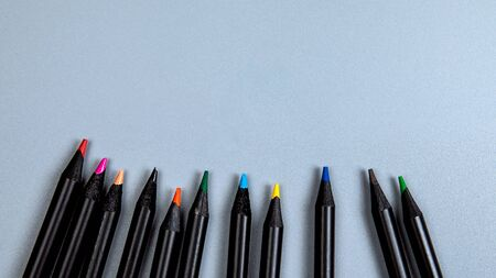 Colored pencils on a grey background. Top view office desk with copy space
